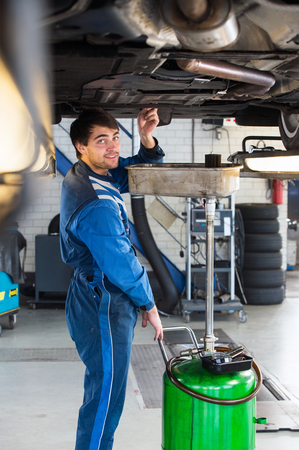 car lift: Reliable looking mechanic, checking the oil of a car on a car lift in a garage Stock Photo