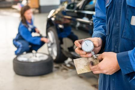 mecanico: Sección media de mecánico calibre celebración analógico con el colega que repara el coche en el fondo en el garaje Foto de archivo