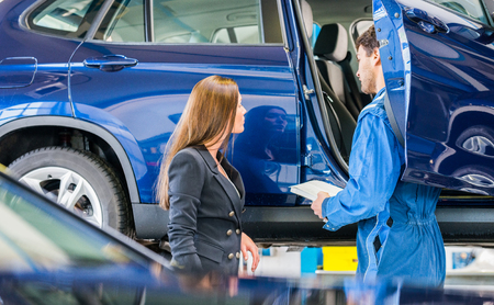 automobile repair shop: Mechanic and female customer discussing problem with car in automobile repair shop Stock Photo