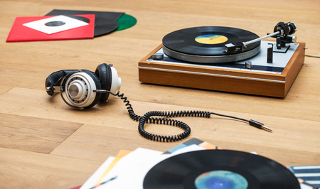 lps: Retro styled image of a record player, vinyl LPs and a head set on a wooden surface