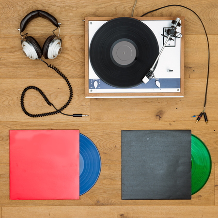 turn table: A vintage, retro, record player and vinyl LP records and set of head phones neatly aligned on a wooden backround Stock Photo