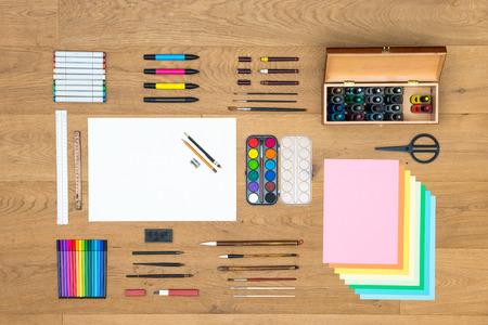 Rozmanité pole umění, řemesla, kreslení a designových předmětů, jako jsou pera, pravítka, fixy, značkovačů, plnící štětce, akvarel a různé listy papíru na dřevěný povrch