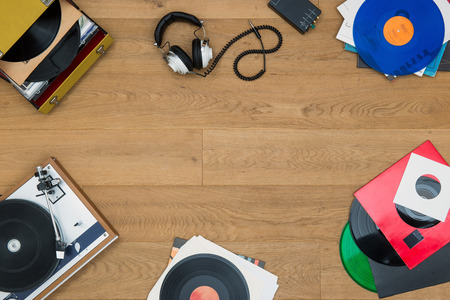 top view of assorted items, associated with vinyl records, record players, music, audio, listening, in a vintage retro style, with copy space in the middle of the image, seen from above Foto de archivo
