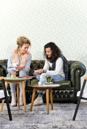 tea table: Young man showing a woman a few photos on his smart phone, sitting on a luxurious couch in a retro styled lounge Stock Photo