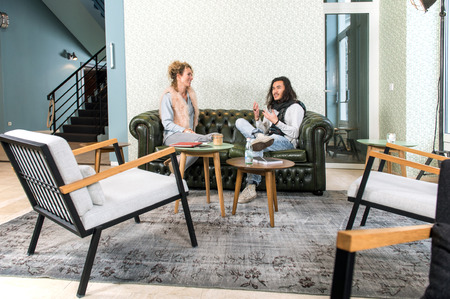 vividly: Two people, a man and a woman, sitting on a chesterfield couch in a trendy, retro styled, lobby of a theater, talking vividly with gestures