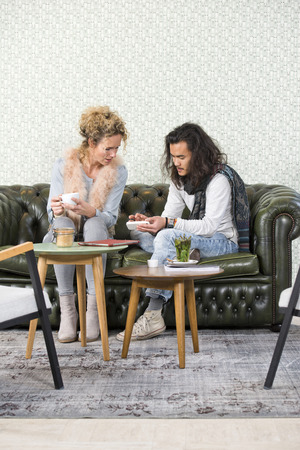 spare time: Friends, sitting on a leather couch, sharing information, and catching up at a trendy and stylish coffe bar