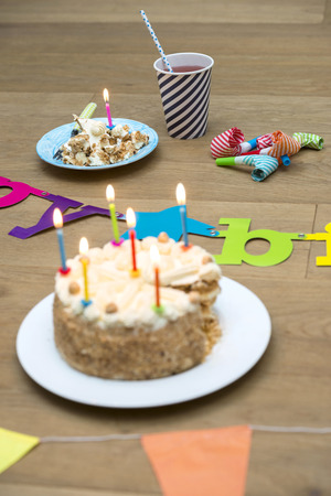 lit collection: Lit candles on birthday cake with decorations on wooden table