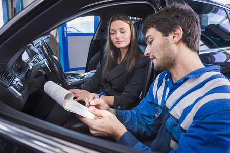 men working: Car expert shows the checklist of repaired items to customer in garage Stock Photo