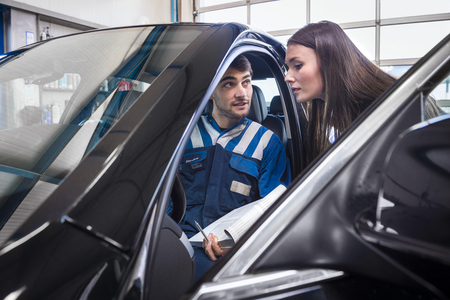 client gets explanaition from the car mechanic over the serviced items of her car. The mechanic sits in the car and points to the dashboard. Standard-Bild