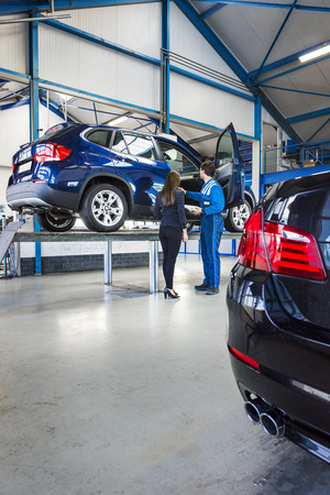 lifted: A car is lifted on a bridge in a car garage, the mechanic stands next to it with the owner Stock Photo