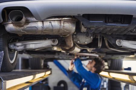 Échappement d'une voiture sur le pont à un atelier de réparation automobile avec un mécanicien-dessous Banque d'images