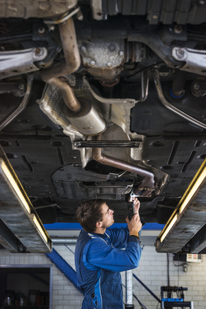 car exhaust: Mechanic underneath a car on a bride and fixing the exhaust