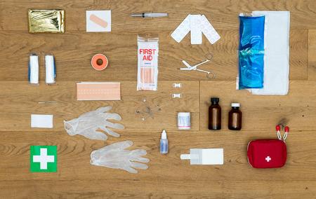 botiquin de primeros auxilios: Los artículos y objetos en un kit de primeros auxilios, perfectamente alineados sobre una superficie de madera, incluidas las pinzas, vendas, yeso, píldoras, calor o compresa fría, manta de aislamiento, cinta adhesiva, guantes de goma, imperdibles y mucho más.
