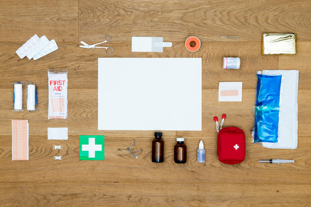 The items and objects in a first aid kit, neatly aligned on a wooden surface, with a blank card for a message or text as copy space available. Items include pliers, bandages, plaster, pills, heat or cold pack, isolation blanket, tape and much more.