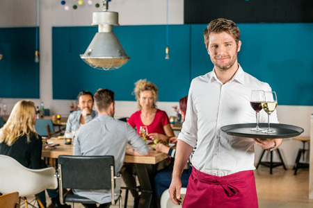 waiter tray: Portrait of confident waiter holding tray at restaurant with customers in background Stock Photo