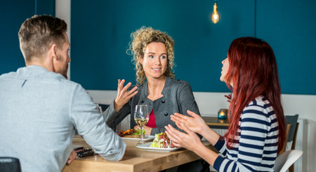 conversing: Young woman talking to friends while having food at restaurant table Stock Photo