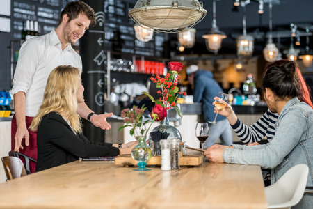 tomando refresco: joven camarero que toma orden de los clientes en la mesa de caf�
