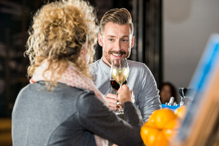 toasting wine: Young man toasting wine with female friend in bar Stock Photo