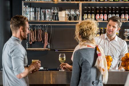 Mannelijke barman praten met klanten bij staafteller