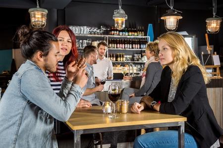 conversing: Young woman looking at friends conversing in bar Stock Photo