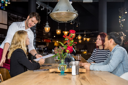 the trendy: Young male waiter presenting menu to customers at table in bar Stock Photo