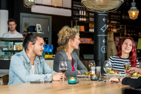 conversing: Male and female friends conversing while having food at restaurant Stock Photo