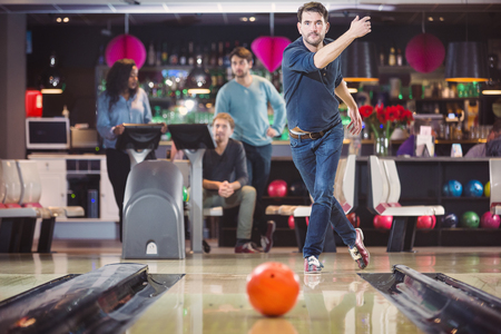 Concentrated man throwing ball in bowling club Stock Photo