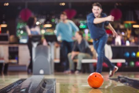 볼링 공은 남자의 던지기 후에 핀으로 굴러 간다.