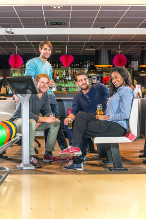 night out: Four friends enjoying a drink at a bowling alley during an active night out Stock Photo