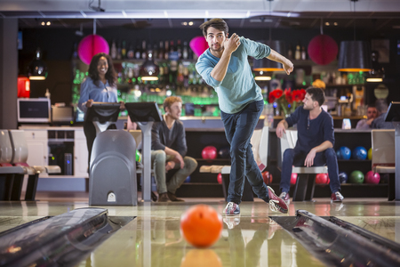 strike: Group of friends are bowling and having fun, young man is throwing the ball at the bowling lane.