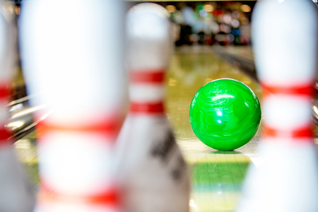 pins: A bowling ball about to hit the pins on a 10 pin bowling alley, seen from the point of view of one of the pins Stock Photo