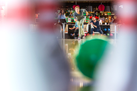 strike: Group of friends on an active night out, bowling in a bowling alley, seen from the point of view of the pins