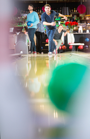 friendly competition: Friends enjoying a competitive and active night out striking down ten-pins at a bowling alley, seen from the point of view of one of the pins Stock Photo