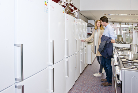 Young couple shopping for a new refrigirator in an electronics and home appliance store with a broad selection of white goods Foto de archivo