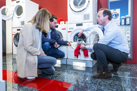 pers: Salesman informing a couple of shoppers about the pers and benefits of a high end washing machine