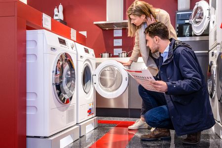 Young couple choosing washing machine in household appliance section at hypermarket