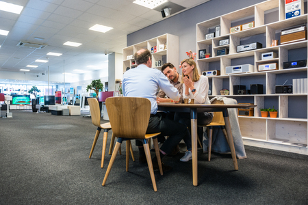 salesman: Salesman assisting young couple at counter in electronics shop Stock Photo