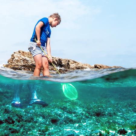 young boy fishing in the sea with a fishing net, near rocks 版權商用圖片