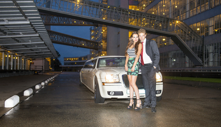 stardom: Young, cute couple, standing in front of a strech limousine in a retro looking industrial facility