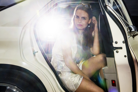 stardom: Pretty woman in the door opening of a limousine, ready to get out, and mingle in the nightlife. Bright lights from behind Stock Photo