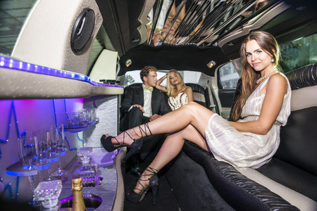 rich people: Pretty woman in a short dress sitting on a comforable sofa inside a luxurious limousine, with a couple of rich and famous Celebrities in the back seat of the car