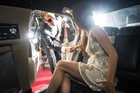 타블로이드 신문과 파파라치 사진 작가에 의해 둘러싸여 레드 카펫 행사 기간 동안 리무진 밖으로 점점 유명한 제트 세트 커플,