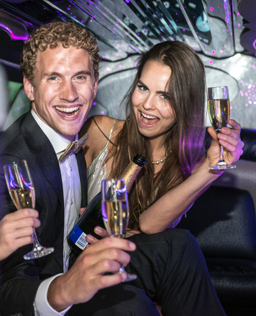decadence: Rich couple drinking champagne in a limousine, having an extravagant party. Stock Photo