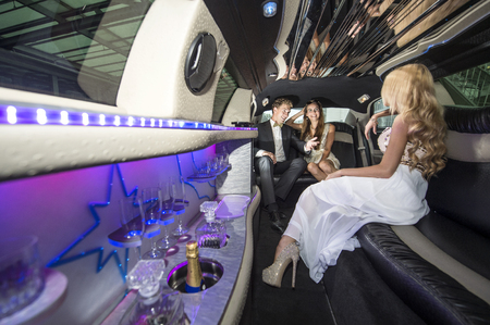 interiour: Three rich and famous people, celebrities, sitting in a luxurious limousine, chatting away, having a good time.