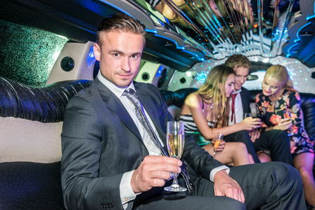 Confident Young Man Holding Champagne Flute In Limousine