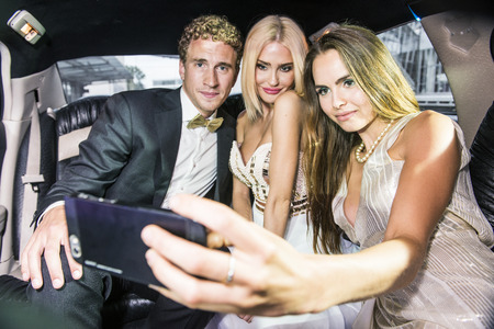 stardom: Three smartly dressed people, ready for an event, taking a selfie with a mobile phone in the back or a luxurious limousine Stock Photo