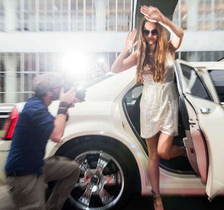 celebrities: Pretty and young celebrity, rushing out of a limousine, trying to escape multiple photographers, shielding her identity with a pair of large sunglasses and her hands. Slight motion blur.