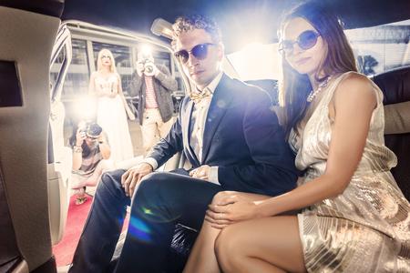 Elegantemente vestido pareja de famosos, listo para salir de una limusina durante un evento de alfombra roja, con varios paparazzi y la prensa sensacionalista espera de ellos.