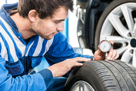 depth gauge: Young male mechanic pressing gauge into tire tread to measure its depth at garage