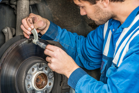 brake disc: Young male car mechanic examining brake disc with caliper in automobile shop Stock Photo